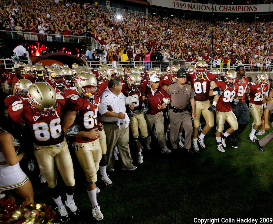 TALLAHASSEE, FL 10/10/09-FSU-Ga. Tech FB09 CH13-Florida State Head Coach Bobby Bowden, center, links arms with his players as they walk on to the field for the Georgia Tech game Saturday at Doak Campbell Stadium in Tallahassee. .COLIN HACKLEY PHOTO