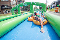 NWA Democrat-Gazette/J.T. WAMPLER Louann Hays of West Fork and her son Rebel, 5, slide Sunday August 30, 2015 down a 1,000-foot-long water slide set up on Dickson Street in Fayetteville. The water slide was brought to Fayetteville by Slide the City, a company based in Salt Lake City. Part of the event's proceeds will benefit Soldier On Service Dogs, a nonprofit organization that raises, trains and gives away service dogs to veterans who have post-traumatic stress disorder or traumatic brain injuries. For more photos of the event go to http://nwamedia.photoshelter.com/