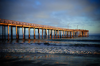 The day's final light rays hit the pier at Cayucos, making a golden spectacle and almost giving the image a painterly look