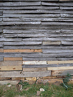 Barn wall with patched aged wooden planks.