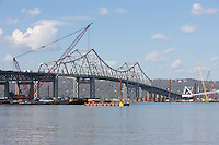 Barges and cranes, under and adjacent to the existing Tappan Zee Bridge, are part of the equipment in place to lay the pilings for the foundation of the new Tappan Zee Bridge, spanning the Hudson River between Westchester and Rockland counties in New York.  The current schedule has the new bridge beginning to carry traffic in 2016 and completed in 2018.