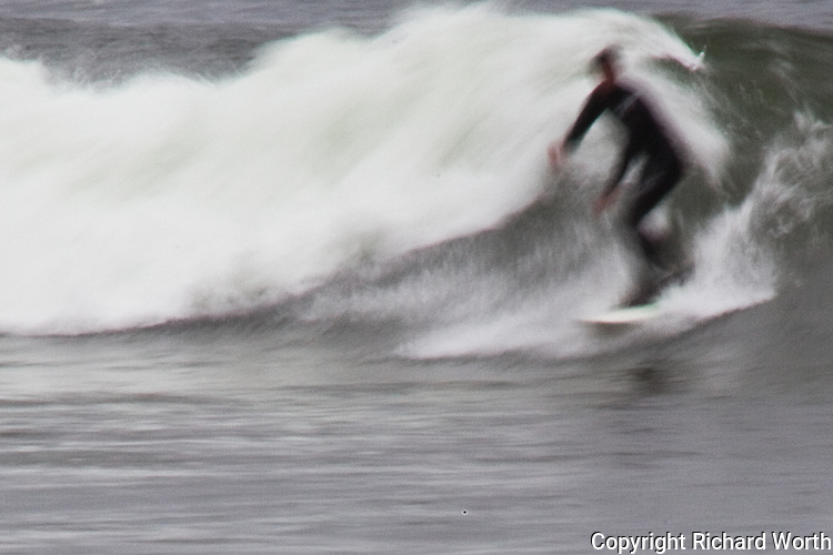 A surfer rides a wave, the motion of both accentuated by slow shutter capture.