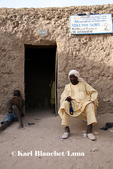 The marabout sitting outside his house in Timbuctu, Mali. His house is also used as a coranic school. The coranic schools in Timbuctu are only open early in the morning and on Saturdays in order to allow pupils to attend the public school.