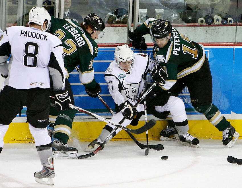 AMERICAN HOCKEY LEAGUE -- Iowa players Junior Lessard (22) and Toby Petersen (19) battle San Antonio's David Spina (17) and Cam Paddock (8) for control of the puck during the game between the San Antonio Rampage and the Iowa Stars, Dec. 8, 2007, at the AT&T Center, San Antonio, Texas. Iowa won 3 - 2 in overtime. (Darren Abate/pressphotointl.com)