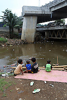 Indonesian children sit next to a polluted river in central Jakarta.<br />