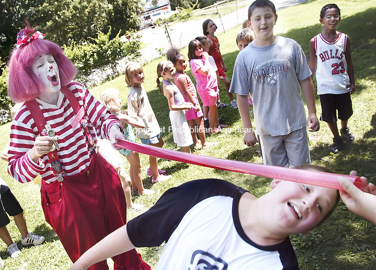 PLYMOUTH, CT-- 31 July 2007--073107TJ05- Valentine the Clown, left, reacts as Sean Wollenberg, 11, limbos under the bar and Ariel Batista, 9, and Eric Orr, 12, from right, all from Plymouth, Conn., watch during a Terryville Park and Recreation summer program at Veterans Memorial Playground in Plymouth, Conn., on Tuesday, July 31, 2007.<br />