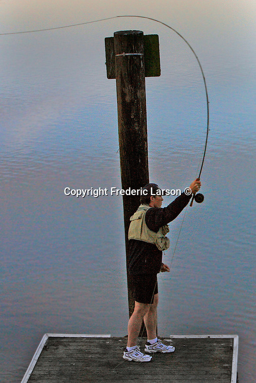 A fishermen practices is his rod and reel fly fishing off a small pier in Richardson Bay, Mill Valley, California.