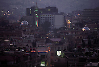 An illuminated portrait of President Bashar al-Assad shines out as dusk settles over Damascus.