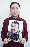 Lazzat Rasul holds a photograph of her brother who was arrested and sent to a camp where he was severaly tortured. Then he was sent to a hospital to heal his wounds. Though after they found out that his family is unable to pay for it he was sent back  to prison without any medical help. <br /> <br /> <br /> Расул Лаззат держит фото братьев Расул Женис. Брат попал в концлагерь, его там жестоко пытали, потом поместили в госпиталь и потребовали огромные деньги на лечение. Таких денег у семьи не был, и его вернули в лагерь обратно, без медицинской помощи.