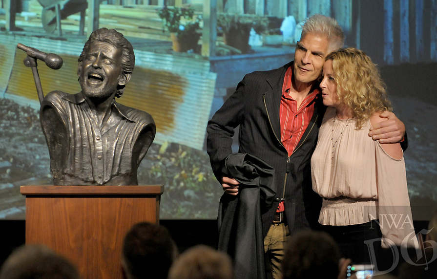 NWA Democrat-Gazette/DAVID GOTTSCHALK Amy Helm (right), daughter of musician Levon Helm, unveils with artist Kevin Kresse Friday, October 12, 2018, a bronze bust of her late father at the David and Barbara Pryor Center for Arkansas Oral and Visual History on the square in Fayetteville. Kresse created the bust that will be placed near the boyhood home of Helm in Marvell. The home was moved from Turkey Scratch to downtown Marvell.