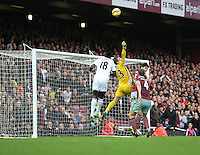 Sunday 07 December 2014<br /> Pictured: Adrian, goalkeeper for West Ham (C) punches the ball away from a Swansea cross, Bafetimbi Gomis of Swansea (L) can't get to it<br /> Re: Premier League West Ham United v Swansea City FC at Boleyn Ground, London, UK.