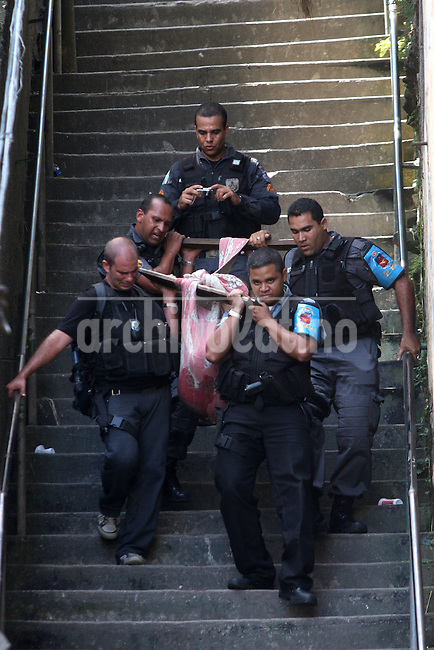 Rio de janeiro State Police Police (PMERJ) carry a body down a stairway from a slum where a shootout took place about 1 hour earlier in Rio de Janeiro, Brazil, Oct. 21, 2009.