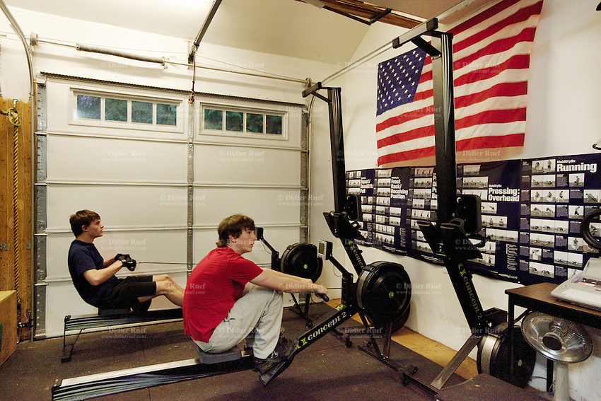 "USA. Washington state. Fall City. ReStart Internet Addiction Recovery program at Heavensfield Retreat Center. Andrew (L) and Josh (R) train on indoor rowers during their Daily Workout sessions in Gym. Both are 20 years old and have dropped out of university because they were highly addictive online video gamers on internet. ReStart is an unique intensive onsite program which offers to participants an opportunity to stay in a retreat center designed to promote insight and renewal, disconnect from digital distractions, and engage in coaching and mentoring while building a blue print for change. The three to six-month reStart program, the first of this kind in the United States, works to help men over 18, suffering from problematic internet, video game, social media and technology use by teaching positive and sustainable lifestyle change in a serene, rural environment surrounded by nature. Modern indoor rowers are often known as ergometers (colloquially erg or ergo), an ergometer being a device which measures the amount of work performed. The national flag of the United States of America, often referred to as the American flag, consists of thirteen equal horizontal stripes of red (top and bottom) alternating with white, with a blue rectangle in the canton (referred to specifically as the ""union"") bearing fifty small, white, five-pointed stars arranged in nine offset horizontal rows of six stars (top and bottom) alternating with rows of five stars. The 50 stars on the flag represent the 50 states of the United States of America and the 13 stripes represent the thirteen British colonies that declared independence from the Kingdom of Great Britain and became the first states in the Union. 9.12.2014 © 2014 Didier Ruef"