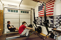 """USA. Washington state. Fall City. ReStart Internet Addiction Recovery program at Heavensfield Retreat Center. Andrew (L) and Josh (R) train on indoor rowers during their Daily Workout sessions in Gym. Both are 20 years old and have dropped out of university because they were highly addictive online video gamers on internet. ReStart is an unique intensive onsite program which offers to participants an opportunity to stay in a retreat center designed to promote insight and renewal, disconnect from digital distractions, and engage in coaching and mentoring while building a blue print for change. The three to six-month reStart program, the first of this kind in the United States, works to help men over 18, suffering from problematic internet, video game, social media and technology use by teaching positive and sustainable lifestyle change in a serene, rural environment surrounded by nature. Modern indoor rowers are often known as ergometers (colloquially erg or ergo), an ergometer being a device which measures the amount of work performed. The national flag of the United States of America, often referred to as the American flag, consists of thirteen equal horizontal stripes of red (top and bottom) alternating with white, with a blue rectangle in the canton (referred to specifically as the """"union"""") bearing fifty small, white, five-pointed stars arranged in nine offset horizontal rows of six stars (top and bottom) alternating with rows of five stars. The 50 stars on the flag represent the 50 states of the United States of America and the 13 stripes represent the thirteen British colonies that declared independence from the Kingdom of Great Britain and became the first states in the Union. 9.12.2014 © 2014 Didier Ruef"""
