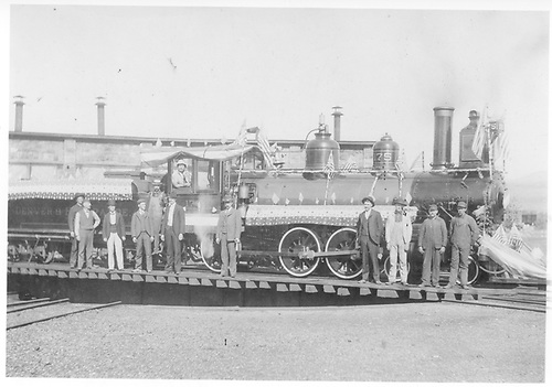 Engine #175 on turntable.  Enigne is decorated patriotically and a dozen men are posing.<br /> D&amp;RGW