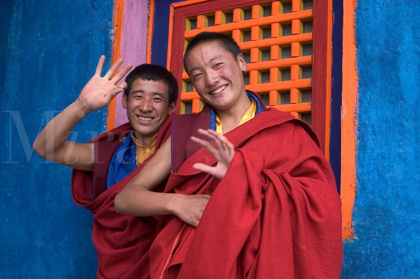 Tibetan Buddhist Monks wave at the Cham dances at the Katok Dorjeden Monastery - Kham, (eastern, Tibet), Sichuan, China