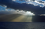 Sunlight streams through clouds and reflects on the sea during springtime in Greece.