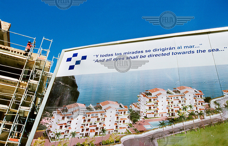 A billboard advertising a new holiday apartment complex stands on a development site. In recent years there has been an explosion of controversial tourist-focused developments in Spain's arid southeastern region causing environmental degradation and placing enormous pressure on the limited amenities in the area. Much of the new housing is sold to foreign buyers who predominantly use or rent the properties as holiday homes.