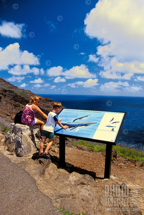 Tourists stop to see and read about the Humpback Whales along the pathway leading to the Makapuu Point lookout and lighthouse. The Humpbacks migrate  annually to hawaiian waters between november and march.