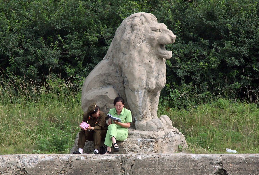 "North Korean women read together next to a stone lion along the river port town of Sinuiju July 8, 2006. China and North Korea are separated by the Yalu River, upon which Chinese tourists take pleaure cruises across the water to  observe their less economically developed neighbors.  North Korea has threatened to take ""stronger physical actions"" after Japan imposed punitive measures in response to its barrage of missile tests and pushed for international sanctions. North Korea has vowed to carry out more launches and has said it will use force if the international community tries to stop it. DPRK, north korea, china, dandong, border, liaoning, democratic, people's, rebiblic, of, korea, nuclear, test, rice, japan, arms, race, weapons, stalinist, communist, kin jong il"