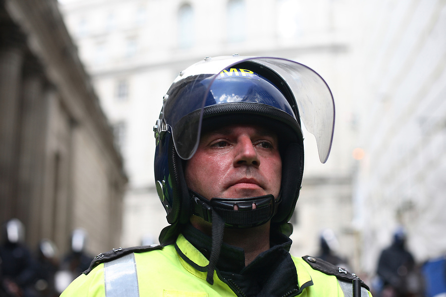 A police officer feels the strain in the heavy riot gear at the G20 Demonstration.