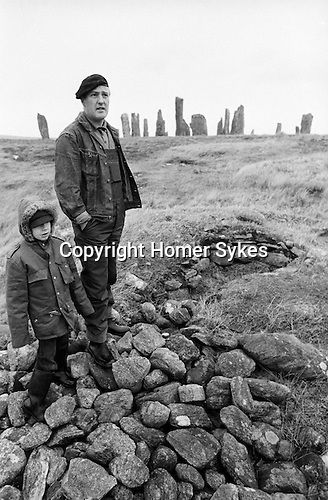 Villagers father and son at Callanish Standing Stones.They are standing on a pile of stones from an excavated burial cyst.  Isle of Lewis, Outer Hebrides, Highland and Islands Scotland 1974