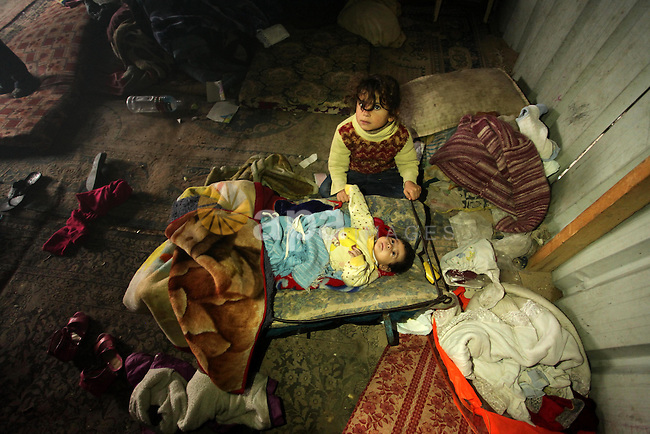 Palestinian children sit inside their dwelling covered with plastic sheet in Khan Younis in the southern Gaza Strip December 19, 2016. Photo by Ashraf Amra