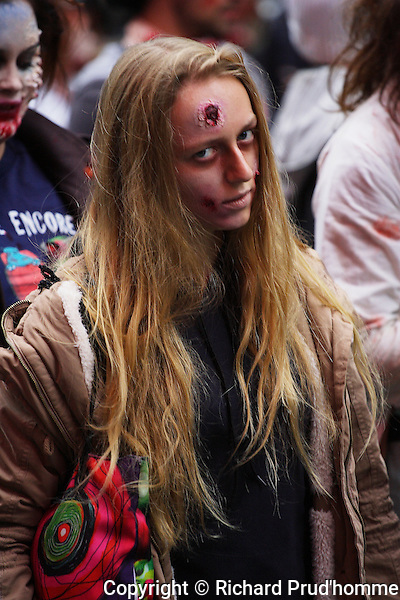 A female zombie with head wound looking at camera