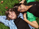 Portrait of two children, sister and young brother, lying down on green grass.