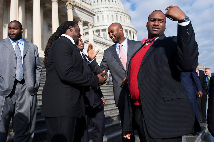 UNITED STATES - JANUARY 19:  Maurice Stovall, center, wide receiver for the Tampa Bay Buccaneers, greets Bucs teammate Davin Joseph, a guard on the offensive line, after a photo on the House Steps.  30 players were invited to the Hill to brief members on the labor dispute and upcoming lockout by the National Football League owners.  Joe Briggs of the NFL Players Association, appears at right.(Photo By Tom Williams/Roll Call)