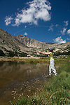 Woman fishing at Lawn Lake on a summer morning in Rocky Mountain National Park, Colorado, USA
