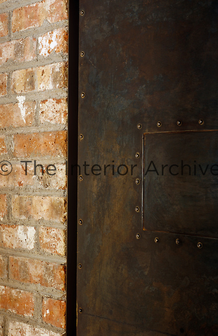 Detail of a brick wall and a studded steel sliding door