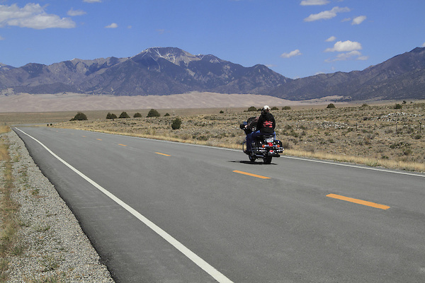 Couple riding motorcycle on the highway leading into Great Sand Dunes National Park, Colorado. John offers private photo trips to Great Sand Dunes National Park and all of Colorado. All year long.