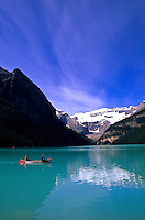 Mountains and tourists on canoe on Lake Louise in Banff Alberta Canada