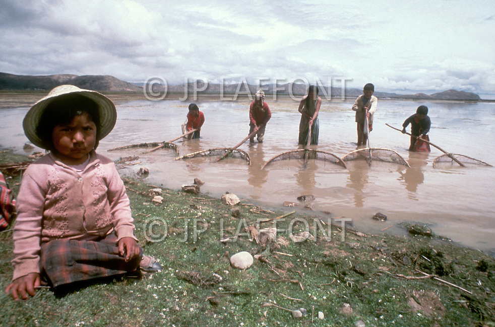 In Bolivia, on the banks of Lake Titicaca, children are employed as fishermen - Child labor as seen around the world between 1979 and 1980 - Photographer Jean Pierre Laffont, touched by the suffering of child workers, chronicled their plight in 12 countries over the course of one year.  Laffont was awarded The World Press Award and Madeline Ross Award among many others for his work.