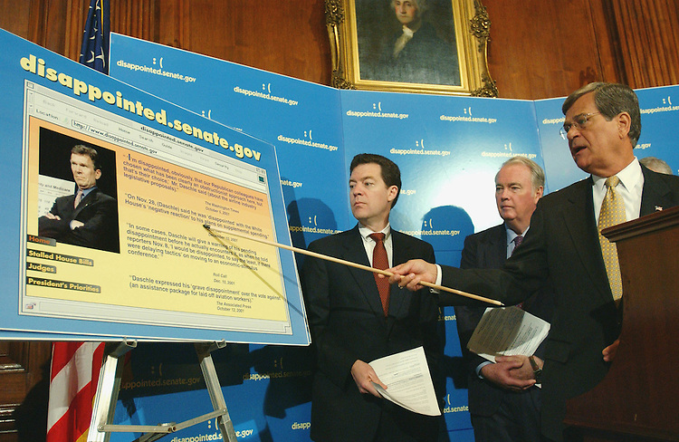 4/12/02.GOP VIEW OF STATE OF THE SENATE--Senate Minority Leader Trent Lott, R-Miss., right, Sen. Sam Brownback, R-Kan., Sen. Rick Santorum, R-Pa., and Sen. Frank H. Murkowski, R-Alaska, during a news conference on the Republican leadership's view of the state of the Senate. Lott is pointing to a poster of a web page accusing the Democratic leadership of delaying tactics on legislation..CONGRESSIONAL QUARTERLY PHOTO BY SCOTT J. FERRELL