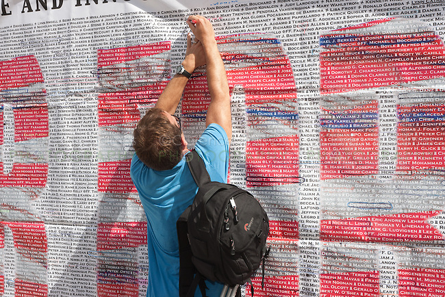 A visitor marks a name on the list of those who perished in the 9/11 terrorist attack of the World Trade Center.  The list is posted on Greenwich Street across from the entrance to the National September 11 Memorial.