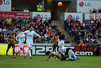 Bafetimbi Gomis of Swansea falls on Laurent Koscielny of Arsenal during the Barclays Premier League match between Swansea City and Arsenal at the Liberty Stadium, Swansea on October 31st 2015