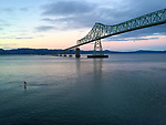 A Stand Up Paddleboarder paddling on the Columbia River just past the Astoria-Megler Bridge in Astoria, Oregon