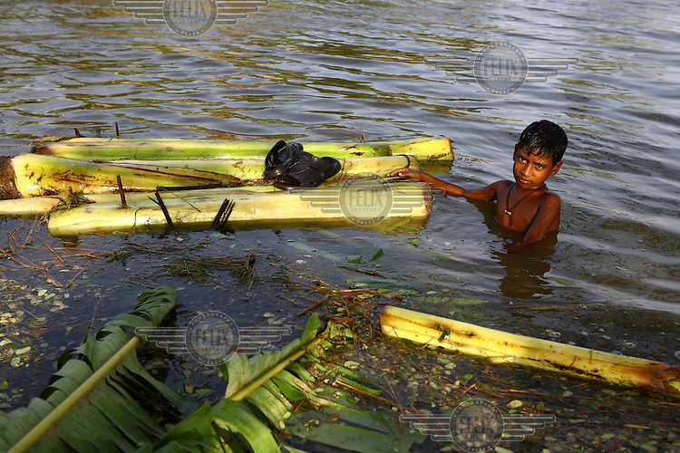 A boy drags tree trunks through the deep floodwaters. Thousands of people were displaced in Shyamnagar Upazila, Satkhira district after Cyclone Aila struck Bangladesh on 25/05/2009, triggering tidal surges and floods..