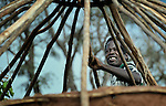 Displaced by war, a man puts a roof on his hut in the Makpandu refugee camp in Southern Sudan, 44 km north of Yambio, where more that 4,000 people took refuge in late 2008 when the Lord's Resistance Army attacked their communities inside the Democratic Republic of the Congo. Attacks by the LRA inside Southern Sudan and in the neighboring DRC and Central African Republic have displaced tens of thousands of people, and many worry the attacks will increase as the government in Khartoum uses the LRA to destabilize Southern Sudan, where people are scheduled to vote on independence in January 2011. Catholic pastoral workers have accompanied the people of this camp from the beginning. NOTE: In July 2011 Southern Sudan became the independent country of South Sudan.