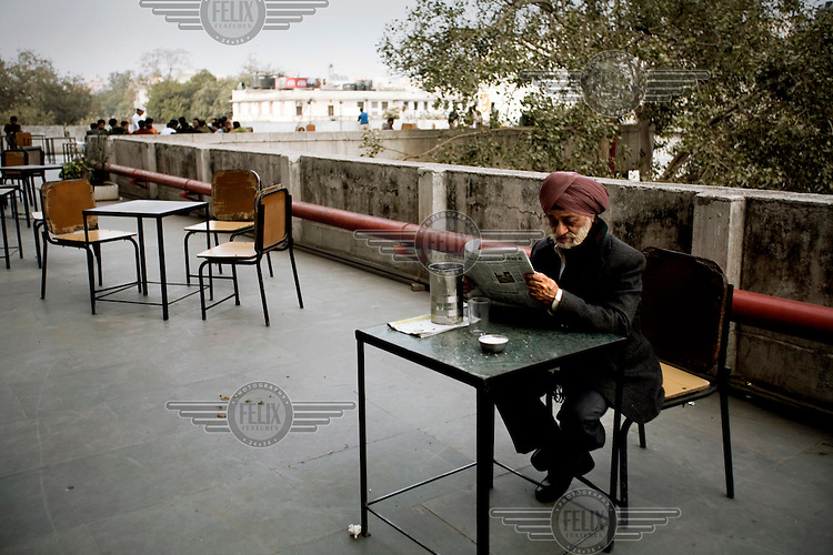 A man reads a newspaper on the roof terrace of the Indian Coffee house, Baba Kharak Singh Marg. The coffee house dates back almost fifty years, first in central Connaught Place, then Janpath and now at the top of a rather shabby shopping centre. Where it is still run by the Indian Coffee Workers Cooperative Society. Once a regular haunt for politicos in Delhi, its clientele is still renowned for being well-read and intellectual.