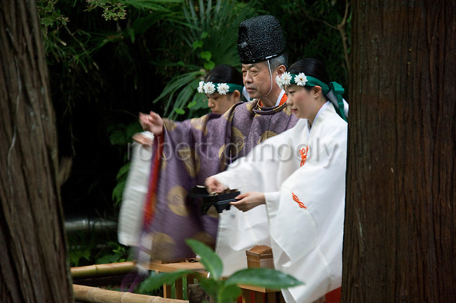 "A priest and maiko attendants release bell crickets that have been dedicated to the shrine ""kami"" (gods) during the suzumushi-hojosai rite that marks the end of the  3-day Reitaisai festival in Kamakura, Japan on  14 Sept. 2012.  The ritual is observed in order to recognize the preciousness of life, releasing the insects by a pond inside the shrine grounds. Photographer: Robert Gilhooly."