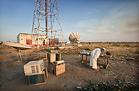 A man repairs electronic equipment outside a new satellite transmitting station. South Sudan.