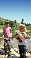 Little girls with big fish in Jackson Hole Wyoming. Sade Wheeldon, girl on right, her father had planted their fish ponds and some fish died in transit. I found they made great photo foder.