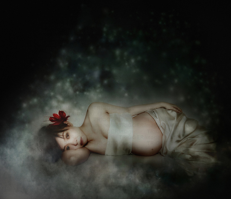 A young pregnant asian woman with a flower in her hair lying resting