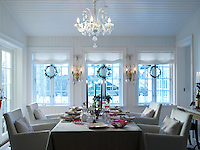 An antique Venetian crystal chandelier hangs above the Christmas dining table, while a row of wreaths provides a festive backdrop against the windows behind