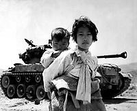 With her brother on her back a war weary Korean girl tiredly trudges by a stalled M-26 tank, at Haengju, Korea.  June 9, 1951.  Maj. R.V. Spencer, UAF. (Navy)<br /> NARA FILE #:  080-G-429691<br /> WAR &amp; CONFLICT BOOK #:  1485