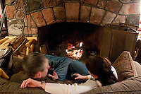 A couple in front of a fire at the Keweenaw Mountain Lodge in Copper Harbor Michigan in winter.