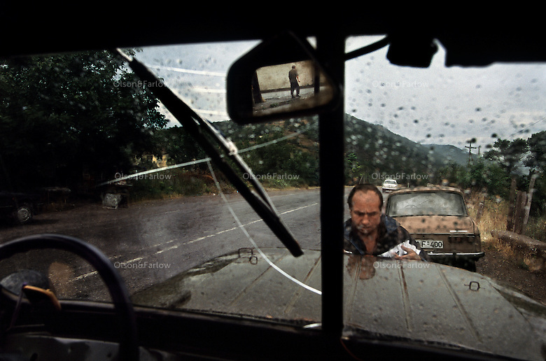 Worn vehicles are proof of the hard life in the Republic of Georgia.  Rain leaks through a canvas roof full of holes. A windshield wiper on one side is just a stick, grating across a broken window.  The driver has unbolted his window and thrown it in the back, but because of the rain, he stops to bolt it back on.  He takes apart the hubs and part of the axle of the jeep to engage the gears.  He tries to keep the jeep running with 4 bald tires, 2 bald spares, an engine that needs a liter of water every ten minutes, and a door that opens only with a screwdriver. He  has 20 gallons of gas sloshing around in the back, and  he hopes the jeep keeps running long enough to take him to his native Khaketi.